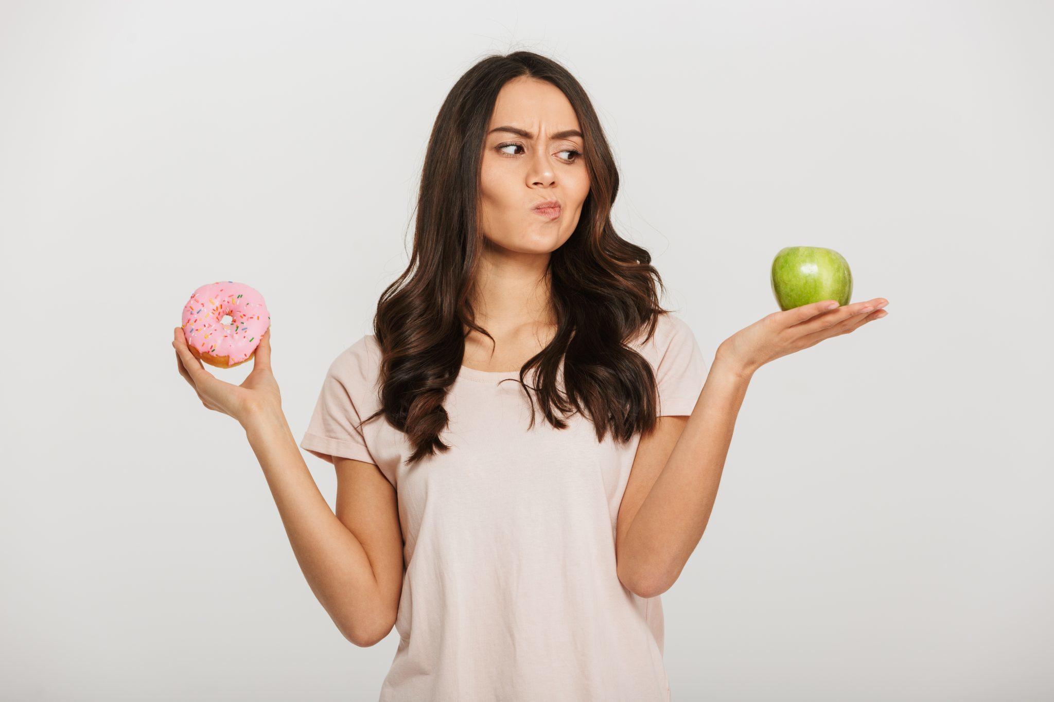 Woman deciding between eating junk food or eating healthy food