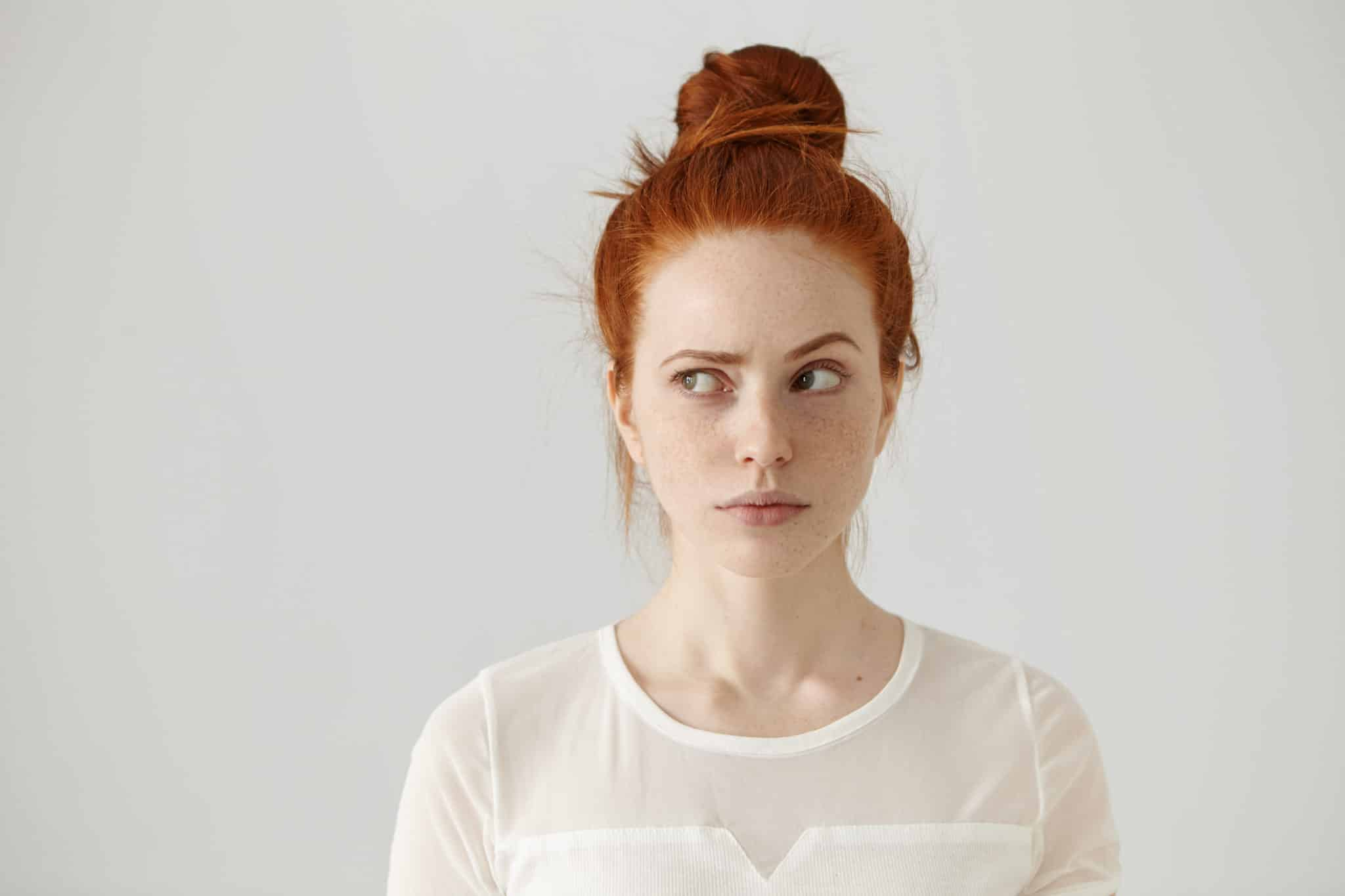 Redheaded girl with a confused look. She is trying to figure out how to create a successful blog.