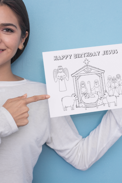 Woman pointing to a Coloring Page with a Nativity Scene that says Happy Birthday Jesus