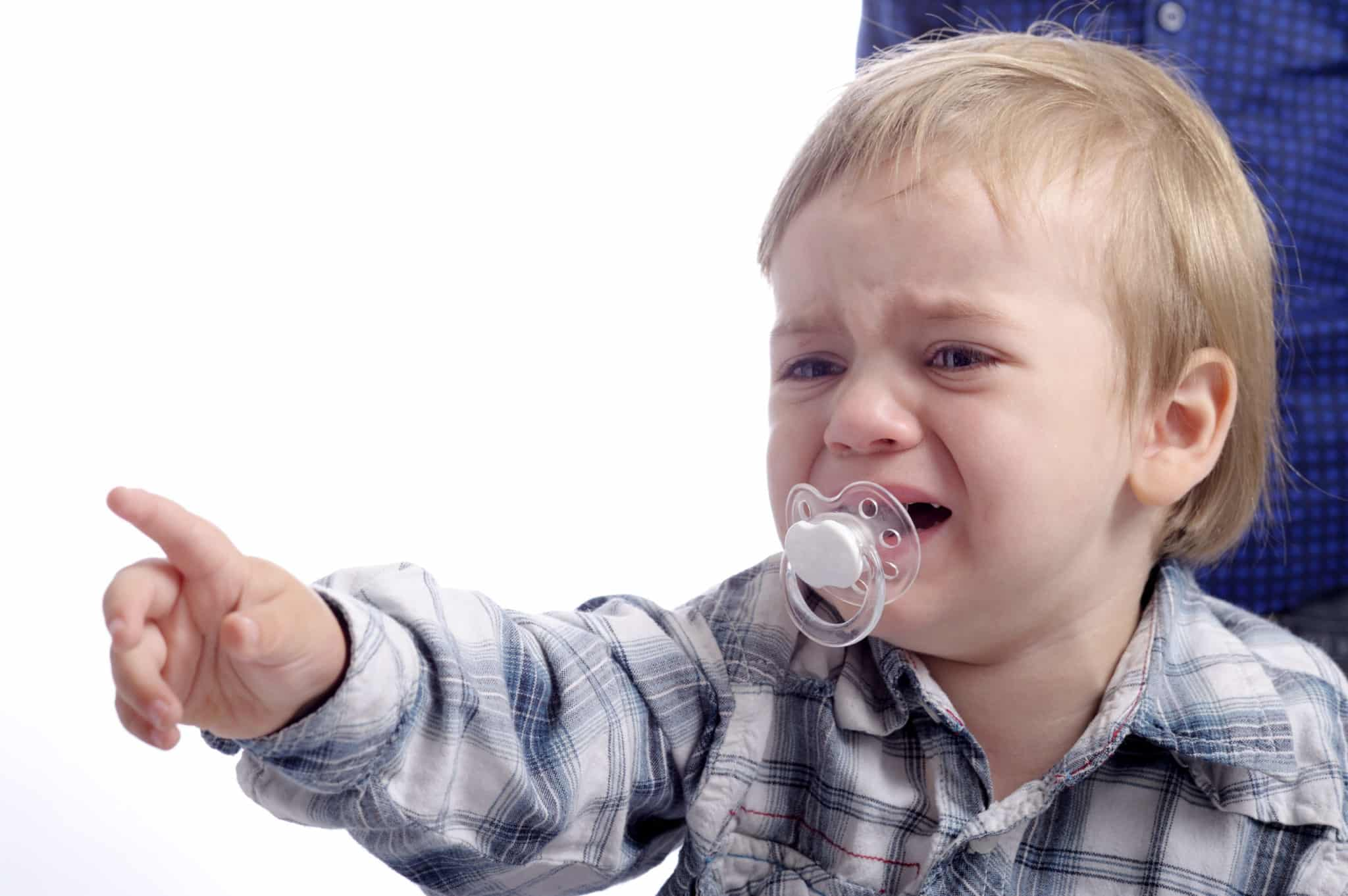 nonverbal crying child pointing with his finger